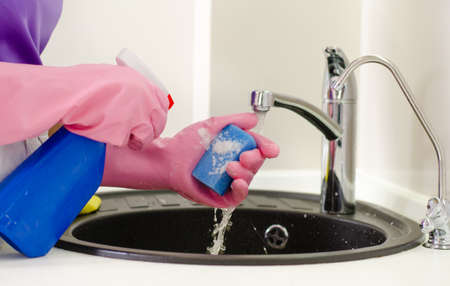 Woman doing the washing up squirting detergent onto a sponge over a sink full of dirty dishes, close up of her gloved hands photo