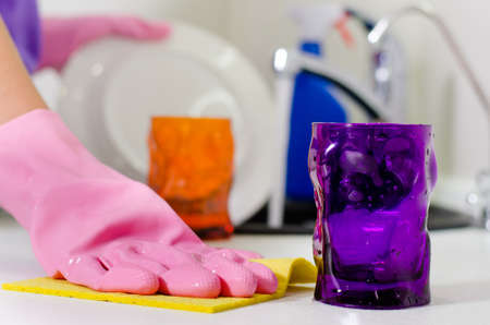 kitchen counter top: Woman wiping the kitchen counter top with a dishcloth as she places the clean glasses and crockery from washing up on the surface Stock Photo