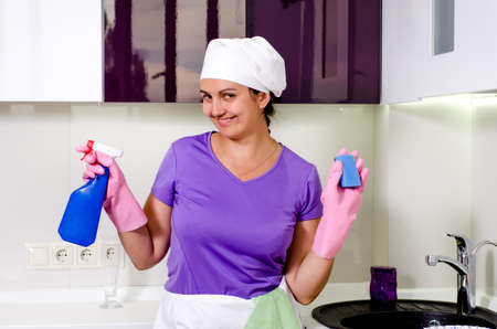 Cute happy playful housewife wearing a white cap over her long hair holding up a spray bottle and sponge as she grins at the camera photo