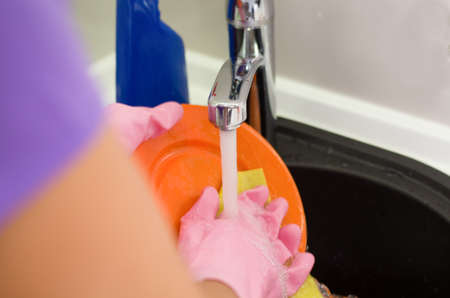 Woman rinsing plates under running water the tap as she does the washing up after a meal, close up of her gloved hands photo