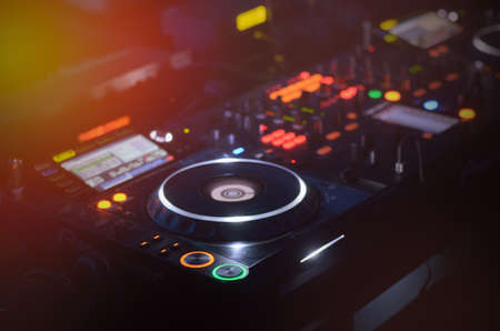 Disc Jockey mixing deck and turntables at night with colourful illuminated controls for mixing music for a party or disco