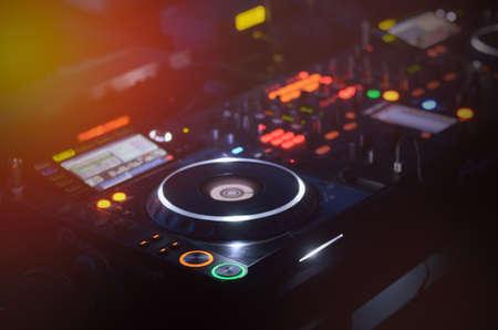 musica electronica: Disc Jockey mezcla de la cubierta y las placas giratorias en la noche con los controles iluminado de colores para mezclar m�sica para una fiesta o discoteca