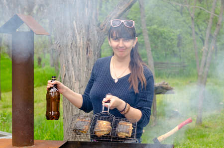 dampen: Smiling woman cooking outdoors over a BBQ holding a grill in one hand and a bottle of water to dampen the flames on the hot fire in the other