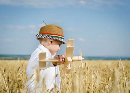 imagines: Trendy young boy playing in a field or ripening golden with a wooden toy plane smiling as he imagines himself flying and looping through the air