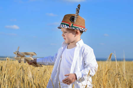 natty: Handsome little boy in a natty straw hat flying a wooden toy plane in a wheat field as he imagines life as a pilot on a sunny summer day Stock Photo