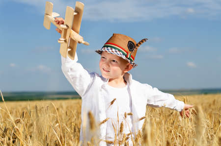 Trendy young boy playing in a field or ripening golden with a wooden toy plane smiling as he imagines himself flying and looping through the air