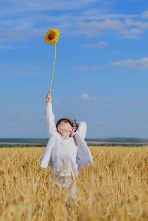 Portrait of a cute little boy wearing white clothes and a rustic hat while holding a sunflower in the middle of a ripe wheat field, under a clear blue sky, in a warm summer day photo