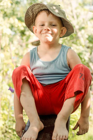 preteen boys: Cheeky young barefoot country boy in red pants and a t-shirt grinning playfully at the camera as he sits on a plank of wood in the garden