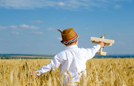 ingenious: Cute little boy flying his toy plane in a wheat field standing in the ripening golden ears of wheat swooping and climbing in the air as he imagines himself to be the pilot