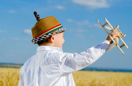 imagines: Young boy in an elegant hat adorned with a feather standing playing with a model airplane as he imagines himself as the pilot on a hot sunny day in open farmland