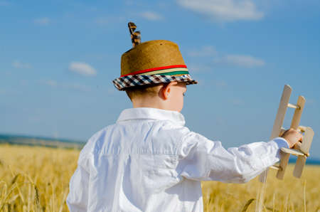Young boy in an elegant hat adorned with a feather standing playing with a model airplane as he imagines himself as the pilot on a hot sunny day in open farmland photo