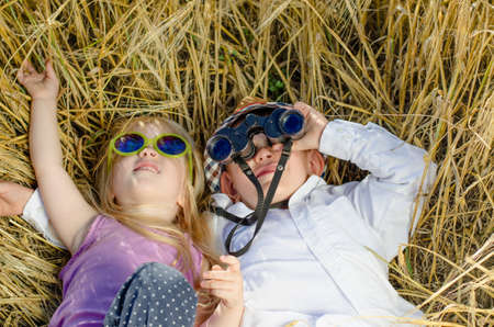 Cute stylish little boy and girl lying on their backs close together in long grass playing with binoculars looking up at the camera