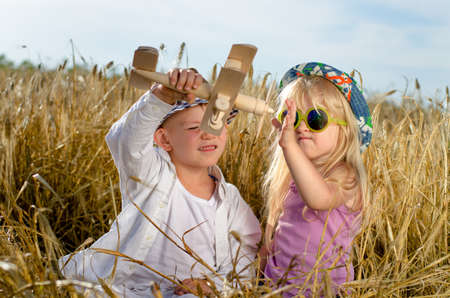 Two young children, a boy and girl in trendy hats, playing together in the summer sunshine with a wooden model plane in a golden wheat field photo