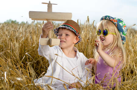 Two young children, a boy and girl in trendy hats, playing together in the summer sunshine with a wooden model plane in a golden wheat field