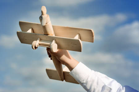 Hand of a child playing with a wooden airplane toy photo