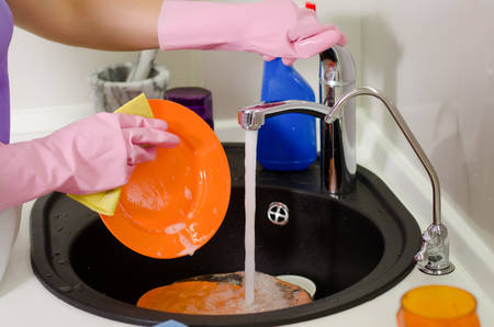 rinsing: Woman rinsing plates under running water the tap as she does the washing up after a meal, close up of her gloved hands Stock Photo