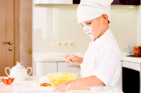Serious little boy chef in a white toque and apron standing at a kitchen counter consulting his recipe book as he adds ingredients to his mixing bowl with a face covered in flour Stock Photo - 29836949
