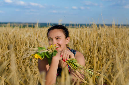concealing: Laughing woman holding a bouquet of colorful yellow flowers in a wheat field of ripening golden wheat partially concealing her face as she enjoys a hot summer day in the countryside