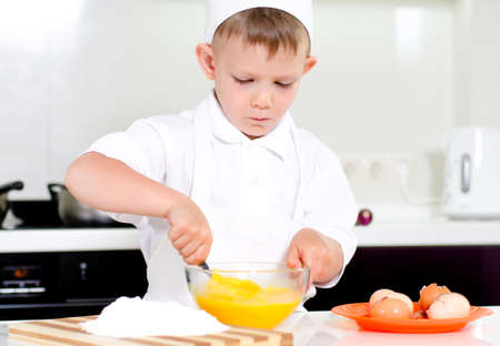 Young boy in a chefs uniform and toque baking whipping eggs in a mixing bowl as he bakes a cake in the kitchen