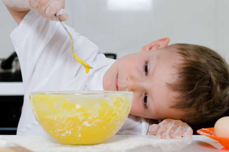 Cute young boy learning to bale a cake carefully watching fresh beaten eggs dripping off the fork into his mixing bowl photo