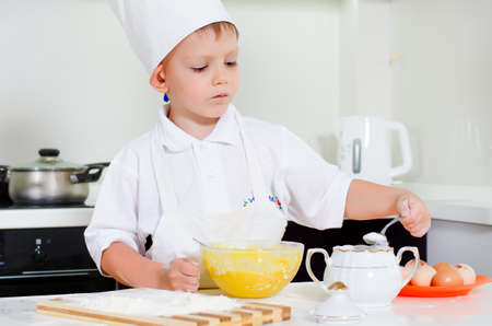 Young boy chef adding ingredients to his mixing bowl with eggs and flour as he bakes a cake for dessert photo