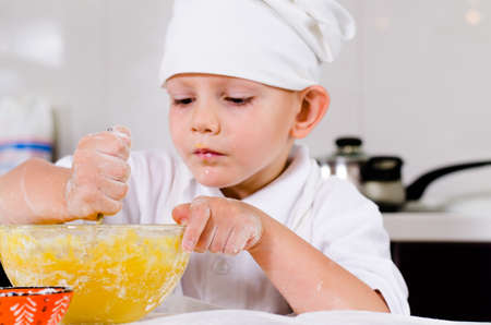 Small boy mixing ingredients for a cake in a bowl concentrating as he carefully stirs the eggs into the flour in his white chefs toque and apron photo