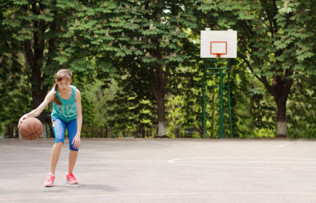Sporty young girl dribbling a basketball in an outdoor court