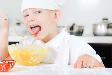 checking ingredients: Small boy learning to cook checking his mixture in the mixing bowl against the ingredients in the recipe book