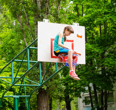 Young girl sitting in hoop in an outdoor basketball court photo