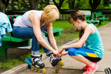 Woman getting help from young girl putting on rollerskates photo