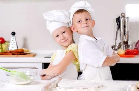Twee leuke trotse jonge chef-koks met een kleine jongen en meisje die zich rijtjes in de keuken in hun witte uniformen en toques met gevouwen armen lachen naar de camera Stockfoto