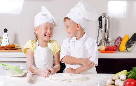 Hooghartige kleine jongen chef-kok die trots met de armen naar beneden te kijken op een schattig klein meisje ook in koks uniform