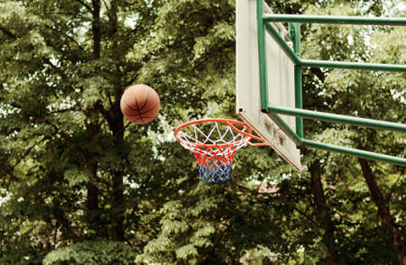 Ball about to go through hoop in an outdoor baskeball court photo