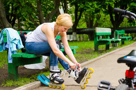 rollerskates: Young girl sitting on a bench removing her rollerskates