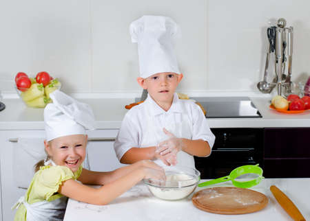 Teamwork in the kitchen as a cute little boy and girl in chefs uniforms learning to bake roll out the dough and get flour ready to sprinkle on top photo