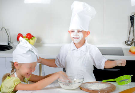 Two cute young children in chefs uniforms and toques learning to bake laughing and joking as they spread flour around the kitchen