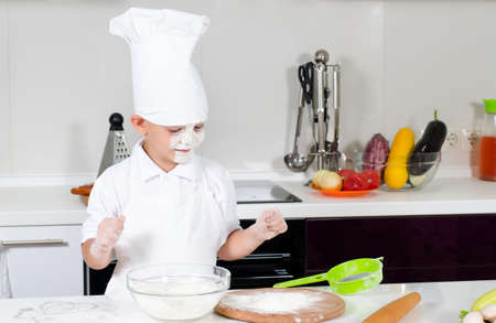 Cute little boy chef in the kitchen with a faceful of flour or batter from the contents of his mixing bowl looking at the camera with a comical expression of disgust photo