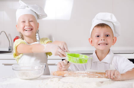 Cheeky happy little boy and girl wearing white chefs uniforms standing at a counter in the kitchen baking a batch of fresh biscuits