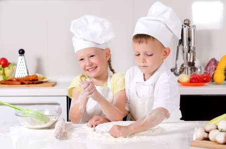 messy kids: Happy little boy and girl wearing a white chefs uniform and hat cooking in the kitchen standing at the counter making a batch of biscuits and rolling the dough
