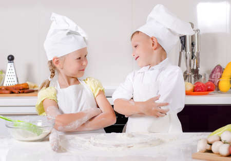 supercilious: Supercilious little boy chef standing proudly with folded arms looking down on a cute little girl also in chefs uniform