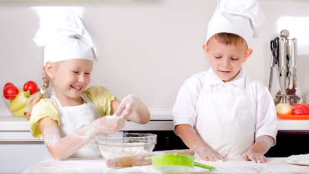 woman baking: Happy little boy and girl wearing a white chefs uniform and hat cooking in the kitchen standing at the counter making a batch of biscuits and rolling the dough