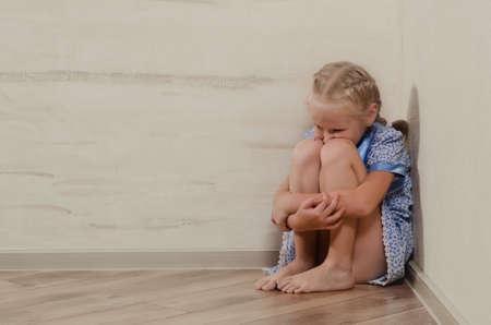 Droevig jong meisje zitten in de hoek gevoel spijt