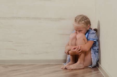 Sad young girl sitting in the corner feeling sorry Stock Photo