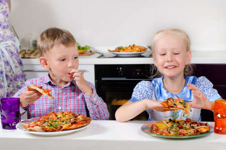 eagerly: Happy little boy and girl sitting in the kitchen eagerly eating homemade Italian pizza