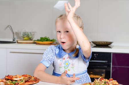 satisfying: Young girl wiping her mouth after a satisfying meal Stock Photo