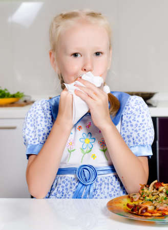 Young girl wiping her mouth after a satisfying meal photo