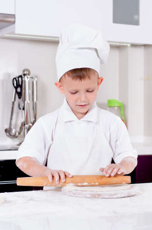 pizza base: Happy little boy in a chefs uniform and hat making homemade pizza giving he stands over the pizza base on a wooden board