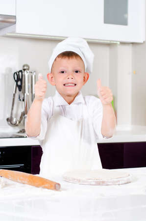 pizza base: Happy little boy in a chefs uniform and hat making homemade pizza giving a thumbs up gesture of success as he stands over the pizza base on a wooden board