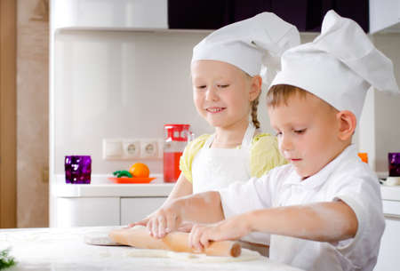 Little girl and boy making homemade pizza working together in the kitchen in their white chefs uniforms and toques rolling out the dough for the base photo