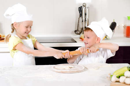 Two young children dressed in white chefs aprons and toques fighting over a rolling pin in the kitchen as they both want to roll out their dough for homemade pizza photo